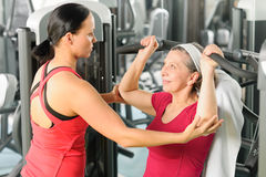 Personal trainer assist senior woman at gym Royalty Free Stock Images