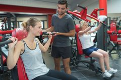 Personal trainer assisting client on chest machine in gym stock images