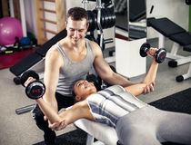 Personal trainer assisting a client Stock Photo