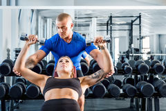 Personal trainer assisting while exercises at the gym. Royalty Free Stock Images