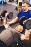 Personal trainer assisting older man in an exercise Royalty Free Stock Photos