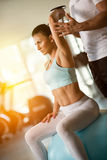 Personal trainer assisting woman lifting dumbbells Stock Photos