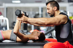 Personal trainer assisting young woman Stock Image