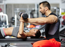 Personal trainer assisting young woman Royalty Free Stock Photos