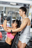 Personal trainer assisting young woman Stock Images