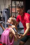 Personal trainer assists a girl in training stock photography