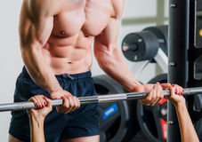 Personal trainer with barbell flexing muscles in gym Stock Photography