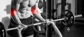 Personal trainer with barbell flexing muscles in gym Stock Image
