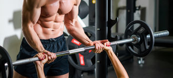 Personal trainer with barbell flexing muscles in gym. Weightlifting and people concept - personal trainer with barbell flexing muscles in gym Royalty Free Stock Photos