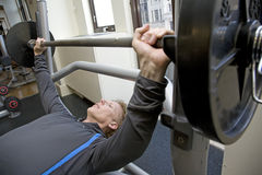 Personal trainer bench pressing weights. In a modern gym Stock Photography