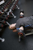 Personal trainer bench pressing weights. / dumbbells in a modern gymnasium Stock Photography