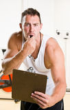 Personal trainer blowing whistle in health club Royalty Free Stock Image