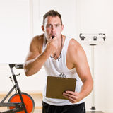 Personal trainer blowing whistle in health club Stock Photos