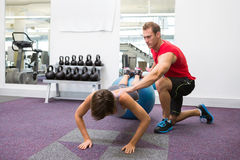 Personal trainer with client doing push up on exercise ball Royalty Free Stock Photo