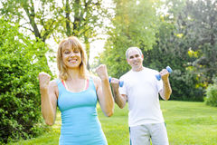 Personal trainer with client exercising. Female fitness instructor exercising with middle aged men in green park stock images