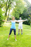Personal trainer with client exercising outside. Female fitness instructor exercising with middle aged men outdoors in green park stock photos