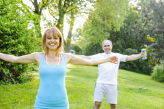 Personal trainer with client exercising outside. Female fitness instructor exercising with middle aged men outdoors in summer park royalty free stock images
