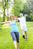 Personal trainer with client exercising in park. Female fitness instructor exercising with middle aged men outdoors in green park royalty free stock images