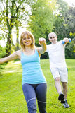Personal trainer with client exercising in park. Female fitness instructor exercising with middle aged men outdoors in green park stock photos