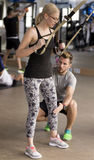 Personal trainer with client. Personal trainer helping client in the TRX corner Stock Photo
