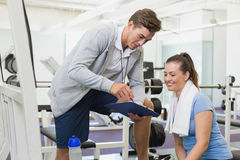 Personal trainer and client looking at clipboard together Royalty Free Stock Photo
