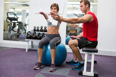 Personal trainer with client sitting straight on exercise ball. At the gym Stock Photo