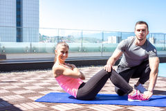 Personal trainer with client who does sit ups. Stock Image