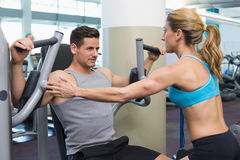 Personal trainer coaching bodybuilder using weight machine Stock Images