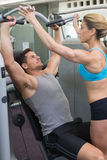 Personal trainer coaching bodybuilder using weight machine Stock Photo