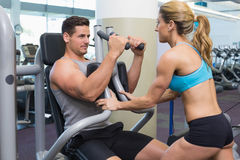 Personal trainer coaching bodybuilder using weight machine Royalty Free Stock Images