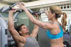 Personal trainer coaching bodybuilder using weight machine Stock Image