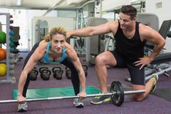 Personal trainer coaching female bodybuilder lifting barbell Stock Photo