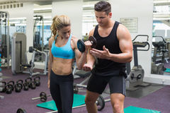 Personal trainer coaching female bodybuilder lifting dumbbell Stock Images
