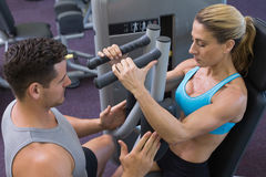 Personal trainer coaching female bodybuilder using weight machine Stock Images