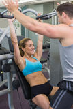 Personal trainer coaching female bodybuilder using weight machine Royalty Free Stock Image