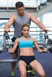 Personal trainer coaching female bodybuilder using weight machine Stock Photos