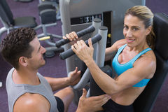 Personal trainer coaching smiling female bodybuilder using weight machine Stock Photo