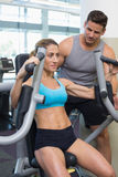 Personal trainer coaching smiling female bodybuilder using weight machine Stock Images