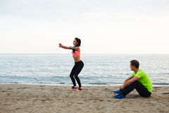 Personal trainer conducts training for girls in the open air. Personal trainer observing how young women doing squat exercises, fitness couple training on the Royalty Free Stock Images