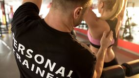 Personal trainer correcting trainee technique in gym, professional assistance royalty free stock image