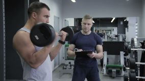 Personal trainer counts number of exercises man has with a barbell on bicep. In gym instructor with sheet takes into account how many times a bodybuilder will stock video