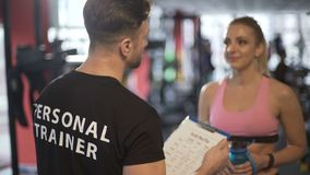 Personal trainer developing training program and explaining it to his client. Stock footage stock video footage