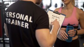 Personal trainer discussing weekly meal plan with female client in gym, support. Stock photo royalty free stock photography