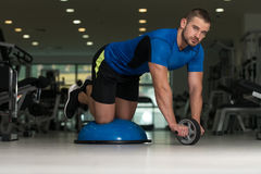 Personal Trainer Doing Exercise On Bosu Balance Ball. Personal Trainer Doing A Exercise For Abs With Bosu Balance Ball As Part Of Bodybuilding Fitness Training Stock Image