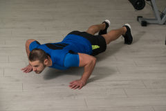 Personal Trainer Doing Push-ups On Floor In Gym Stock Images