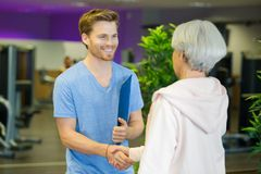 Personal trainer and elderly fit woman shaking hands royalty free stock photography
