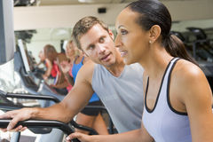 Personal Trainer Encouraging Woman Using Treadmill Royalty Free Stock Photography