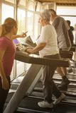 Personal trainer exercise helps elderly couple. Senior couple on. The jogging machine stock photos