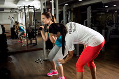 Personal trainer exercise and shows how to workout training. At gym Stock Photo