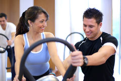 Personal trainer explaining a vibration plate. Instructor in a gym explains a vibration plate to a woman Stock Image